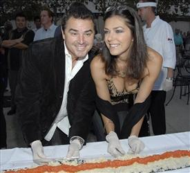 Christoper Knight and model Adrianne Curry pose together as they help to create a 100 foot long tuna roll sushi at the Sashi restaurant opening in Manhattan Beach, Calif. on Thursday, Aug. 28, 2008.