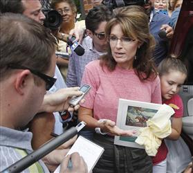 Former Alaska Gov. Sarah Palin, holding a booklet depicting Paul Revere, speaks briefly with the media as she tours Boston's North End neighborhood.