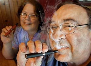 Cliff Phillips, a 61-year-old retiree and former smoker, and his wife, Vali, enjoy electronic cigarettes at their home in Cuba, Ill.