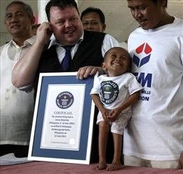 Junrey Balawing smiles as he is presented by Craig Glenday, second from left, with a Guinness World Records certificate for being the world's shortest living man.