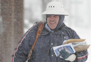 Letter carrier John Vazquez braves the snowy weather as he delivers mail on his route Saturday, March 8, 2008 in Columbus, Ohio. A foot of snow buried parts of the Ohio and Tennessee valleys early Saturday, shutting down travel and many public events. Blizzard warnings remained in effect in Ohio,...