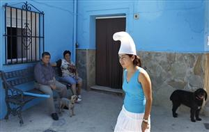 A couple look to a woman dressed up as smurfette in the village of Juzcar, near Ronda, southern Spain, on Thursday, June 16, 2011.The facades of the houses of Juzcar, one of the traditionals white villages of southern Spain, are being painted blue as part of a global promotion...