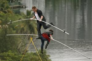 Delilah Wallenda, right, lowers her head as her son Nik Wallenda, left, crosses over her during their high-wire act in San Juan, Puerto Rico, Saturday June 4, 2011.