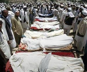 Villagers stand around the covered bodies of people killed when gunmen opened fire on a wedding party in Dur Baba district of Nangarhar province, Afghanistan, June 9, 2011.