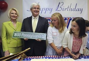 Former House Speaker Newt Gingrich, holds one of his presents, a road sign with the White House address on it, during his 68th birthday party in Atlanta yesterday.