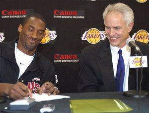 Los Angeles Lakers' Kobe Bryant, left, signs his contract, as general manager Mitch Kupchak looks on in this July 15, 2004, file photo at the team's training facility in El Segundo, Calif. Intentional or not, Kobe Bryant seems to be doing everything he can to pressure the Los Angeles Lakers...