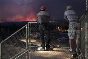 Los Alamos residents Ross Van Lyssel (left) and Steve Bowers watch flames from the Las Conchas fire in Los Alamos, NM, yesterday.