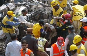 Pakistani rescue workers remove a dead body from the site of a bomb explosion at the office of the Federal Investigation Agency in Lahore, Pakistan on Tuesday, March 11, 2008. Bombs hit the federal police headquarters and a house in the eastern city of Lahore on Tuesday, killing at least...