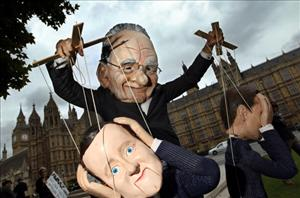 A demonstrator dressed in a Rupert Murdoch mask controls a puppet of British Prime Minister David Cameron.