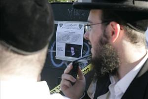Members of the orthodox Jewish community gather near a poster with information about Leiby Kletzky, a missing boy in Brooklyn, Wednesday, July 13, 2011.