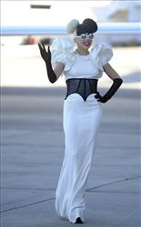Lady Gaga waves as she walks across the tarmac upon arrival in Sydney, Australia, Saturday, July 9, 2011.