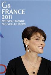 French President Nicolas Sarkozy's wife, Carla Bruni-Sarkozy smiles after a group photo at Le Ciro's Restaurant during the G8 summit in Deauville, France, Friday, May 27, 2011.