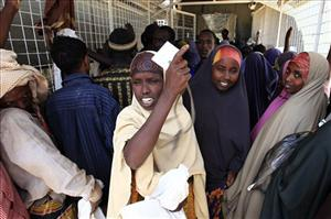 Newly arrived refugees wait to receive their rations at a food distribution center of the Dagahaley refugee camp near the Kenya-Somalia border in Dadaab, Kenya, Saturday, July 16, 2011.