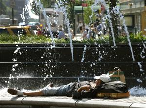 A man lays down next to the fountains at Columbus Circle on July 19, 2011 in New York to try and beat the heat.
