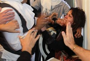 Hands from hotel employees trying to grab her, and foreign journalist attempting to protect her, surround Iman al-Obeidi, right, after she showed her wounds to the press.