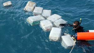 A diver brings cocaine from the scuttled drug sub to the surface.