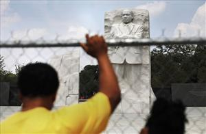 Visitors to the Rev. Martin Luther King Jr. Memorial stand behind security fencing on the National Mall in Washington Sunday, Aug., 21, 2011.