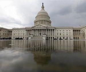 As a rain moves in, the Capitol building is reflected in a pool of water on Capitol Hill in Washington, Wednesday, July 13, 2011.