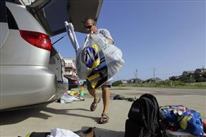 Todd Ketch of Woodbridge, Va., packs up his family's belongings as they prepare to evacuate in Nags Head, N.C., Thursday, Aug. 25, 2011.