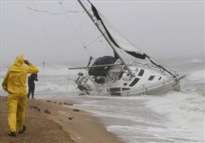 A stranded sailboat founders in the surf along the Willoughby Spit area of Norfolk, Va.