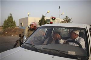 A rebel fighter, left, checks a car at a checkpoint between Tarhouna and Bani Walid, Libya, Monday, Sept. 5, 2011. Negotiations over the surrender of one of Moammar Gadhafi's remaining strongholds have collapsed, and Libyan rebels were waiting for orders to launch their final attack on the besieged town of...