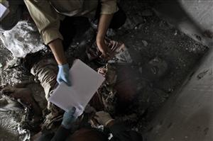 Afghan medics take finger prints of one of the six Taliban militants killed during a gun battle with Afghan and NATO forces in Kabul, Afghanistan, Wednesday Sept. 14, 2011.