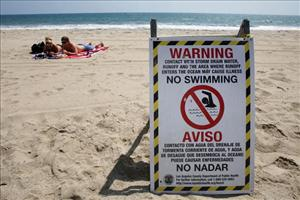 A sign warns people not to swim in a polluted beach in this file photo.