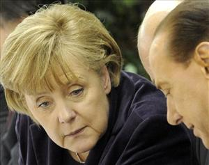 German Chancellor Angela Merkel speaks with Italy's Prime Minister Silvio Berlusconi at an EPP party meeting ahead of an EU summit in Brussels, Thursday, Dec. 16, 2010.