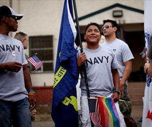 Joseph Martinez (C) an active duty sailor in the Navy, prepares to march during the San Diego gay pride parade July 16, 2011 in San Diego, California.