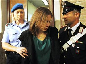 Amanda Knox, center, is escorted as she arrives for an appeal hearing at the Perugia court, central Italy, Monday, Oct. 3, 2011.