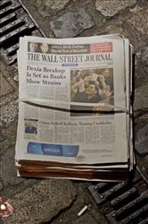 Copies of the European edition of the Wall Street Journal lie on a street in London.