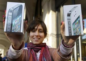 A fan from Reading, England holds up her purchase of two iPhone 4S's outside the Apple Store in Covent Garden.