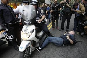 A New York City police officer runs over a National Lawyers Guild observer as Occupy Wall Street demonstrators march through the streets near Wall Street, Friday, Oct. 14, 2011.