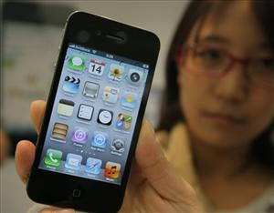 The new iPhone 4S (no yellow screen here)  is shown by a customer at a shop in Tokyo.
