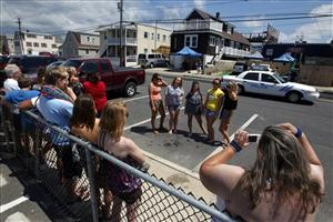 A large crowd gathers as some take photographs outside the television home where the cast members of MTV's Jersey Shore were conducting interviews Thursday, Aug. 4, 2011, in Seaside Heights, NJ.