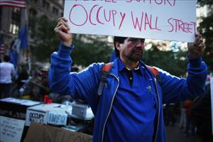 A man holds a sign on the edge of Zuccotti Park in the Financial District  where 'Occupy Wall Street' protesters are living on October 17, 2011 in New York City.