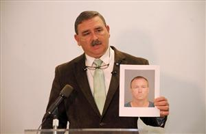 Sheriff Chuck Wright holds a mug shot of a suspect charged with kidnapping, first-degree criminal sexual conduct and grand larceny after an attack on a woman. Wright urged women to start packing heat.