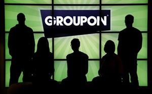 In this file photo, employees at Groupon pose in silhouette with the company logo in the lobby of the online coupon company's Chicago offices.