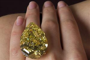 Aa Sotheby's employee displays the Sun-Drop diamond.