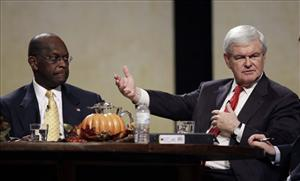 Former House Speaker Newt Gingrich speaks during the Thanksgiving Family Forum in Des Moines as Herman Cain looks on.
