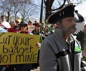 In this March 8, 2010 file photo, Tea Party member Greg Hernandez, of Quicksburg, Va., wearing a tri-corner  hat and tea bag,  listens to speakers during a rally at the Capitol  in Richmond, Va.