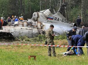 Forensic experts examine a body near a wreckage of a Tu-134 plane that crashed near Petrozavodsk, Russia, in June, killing 47 people.