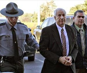 This Nov. 5, 2011 file photo shows former Penn State football defensive coordinator Jerry Sandusky, center, wearing handcuffs as he is escorted to see a judge in State College, Pa.