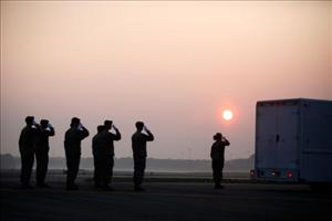 A US  Army carry team at Dover Air Force Base salutes after a mortuary vehicle is loaded containing the remains of US troops who were killed in action.