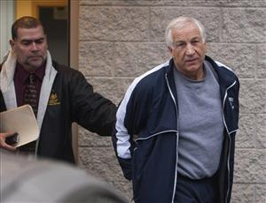 Former Penn State assistant coach Jerry Sandusky leaves the office of Centre County District Justice Daniel A. Hoffman under state police escort after he was re-arrested on new sex assault charges.