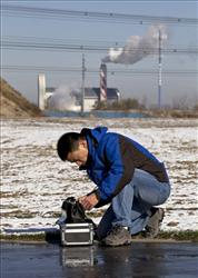 Resident Tan Liang sets up a PM2.5 detector near a garbage-burning facility near his residential compound in Beijing.