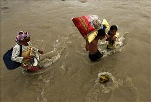 Flash flood victims cross a river after receiving relief goods in Iligan city, southern Philippines on Christmas day Sunday, Dec. 25, 2011.