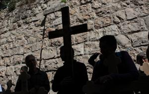 Christian pilgrims carry wooden crosses along the Via Dolorosa duringa Good Friday procession in Jerusalem.