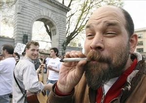 Pro-marijuana activist Rich Paul takes a puff of a marijuana joint in front of the Statehouse in Concord, N.H., Tuesday, April 20,2010.