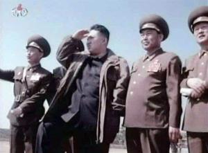 In this undated image made from KRT video, North Korea's new leader Kim Jong Un, third from right, watches jet fighters with North Korean officials.